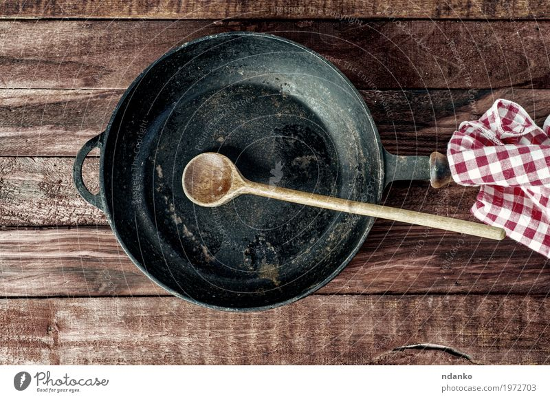 Black iron pan with a wooden handle and a spoon Dish Wood Brown Above Metal Table Clean Kitchen Cloth Restaurant Crockery Steel Top Household Tablecloth