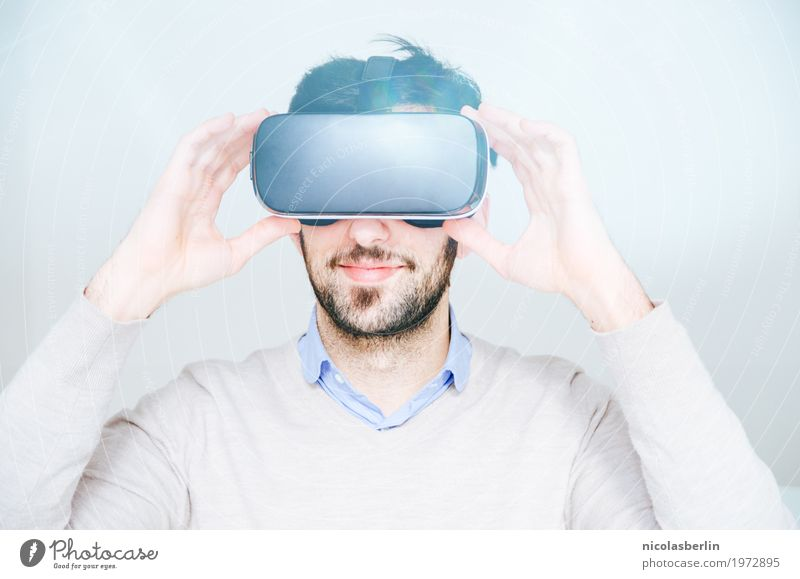 Young man wearing VR glasses and smiling on white background Virtual Joy Smiling virtual reality virtual reality simulator Playing Computer games Success Office