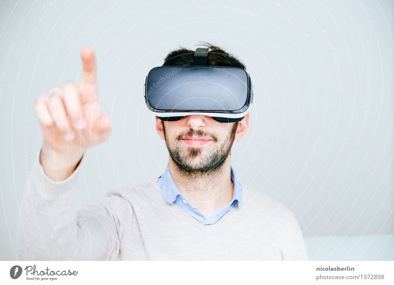 Medium adult man wearing virtual reality simulator glasses pointing finger and white background VR glasses Technology Forefinger Playing Computer games Smiling
