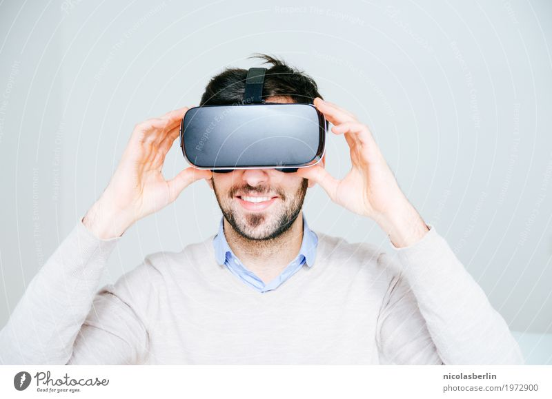 Young man wearing VR glasses and smiling Design Joy Playing Expedition Fitness Sports Training Office Media industry Advertising Industry Business Success
