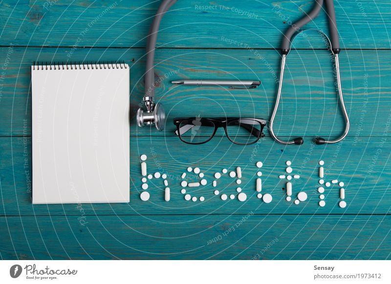 Health concept - pills, stethoscope on the wooden desk Health care Medication Reading Desk Table Science & Research Doctor Workplace Office Hospital Paper Pen