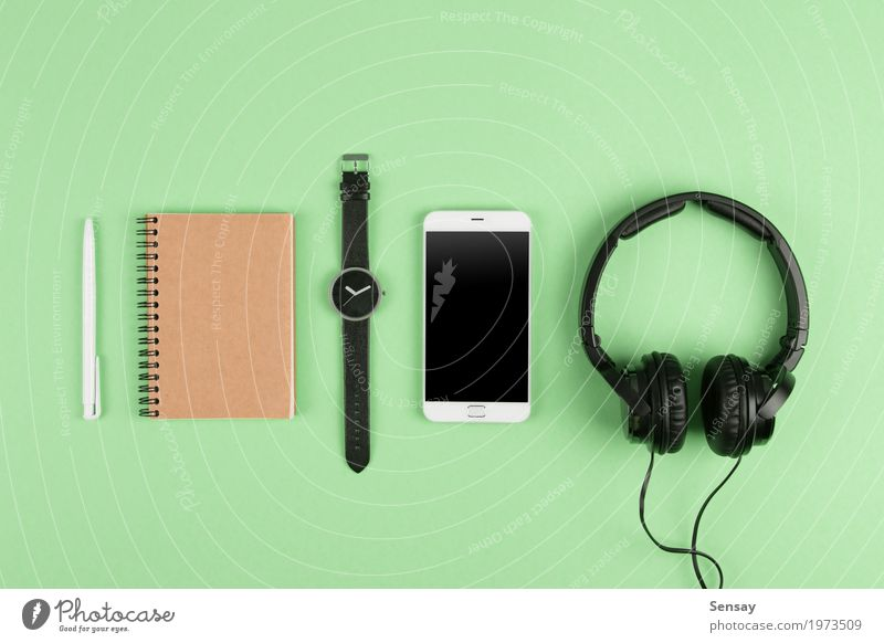 Smartphone, notepad, headphones on the color back Green White Business Above Copy Space Music Technology Vantage point Table Computer Paper Telephone Internet
