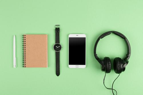 Smartphone, notepad, headphones on the color back Table Music Business Telephone PDA Computer Screen Technology Internet Media Paper Listening Above Green White
