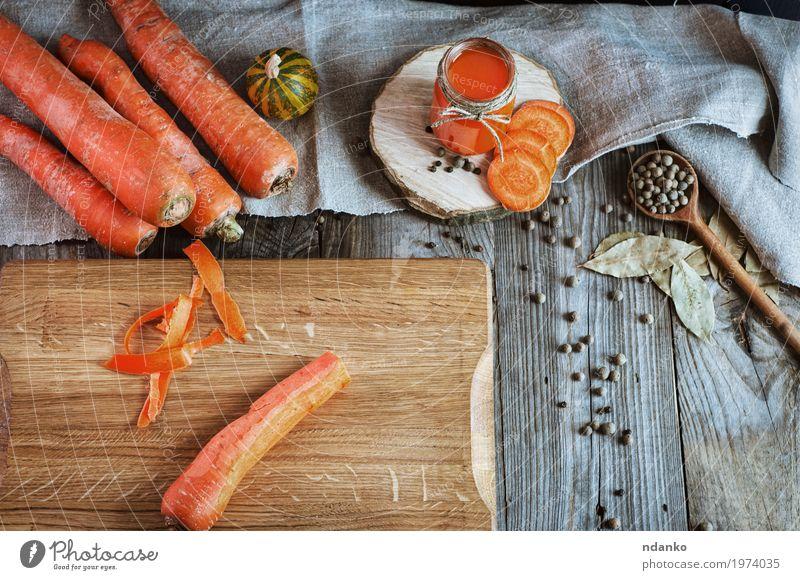 Fresh carrots on the chopping board Vegetable Herbs and spices Nutrition Vegetarian diet Diet Beverage Juice Bottle Glass Spoon Table Wood Old Above Juicy Gray