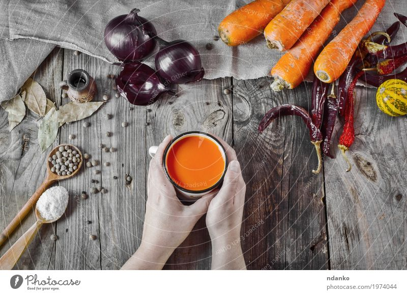 cup of carrot juice in female hands on a gray wooden surface Vegetable Herbs and spices Nutrition Drinking Cold drink Juice Cup Spoon Table Woman Adults Hand 1