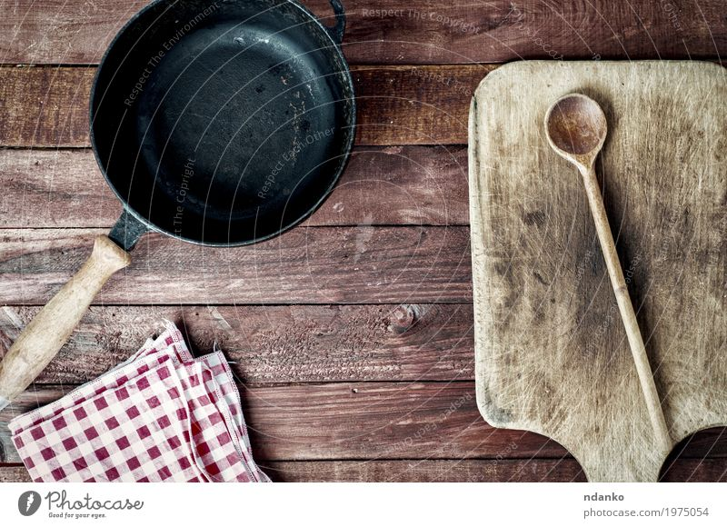 empty black metal pan and cutting board on a wooden surface Pan Spoon Design Table Kitchen Tool Cloth Wood Metal Above Clean Brown Black tableware Tablecloth