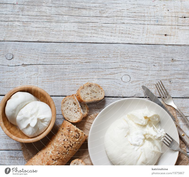 Italian cheese burrata with bread on a wooden background Cheese Dairy Products Dough Baked goods Bread Nutrition Vegetarian diet Italian Food Plate Bowl Fork
