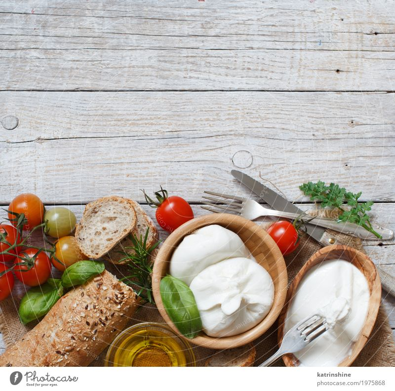 Italian cheese burrata with bread, vegetables and herbs Cheese Dairy Products Vegetable Bread Herbs and spices Nutrition Vegetarian diet Italian Food Bowl Fork