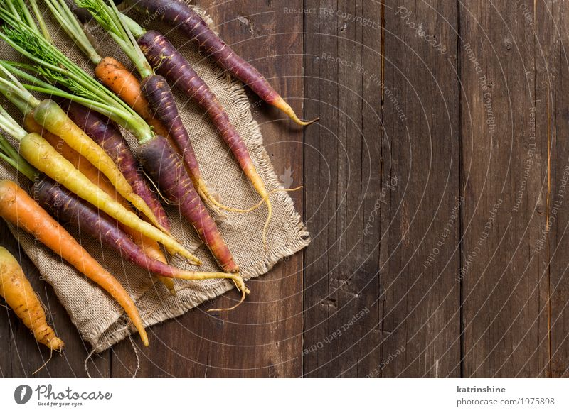 Fresh organic rainbow carrots on a wooden table Vegetable Nutrition Vegetarian diet Brown Yellow Carrot Farmer food Harvest healthy market orange Organic Raw