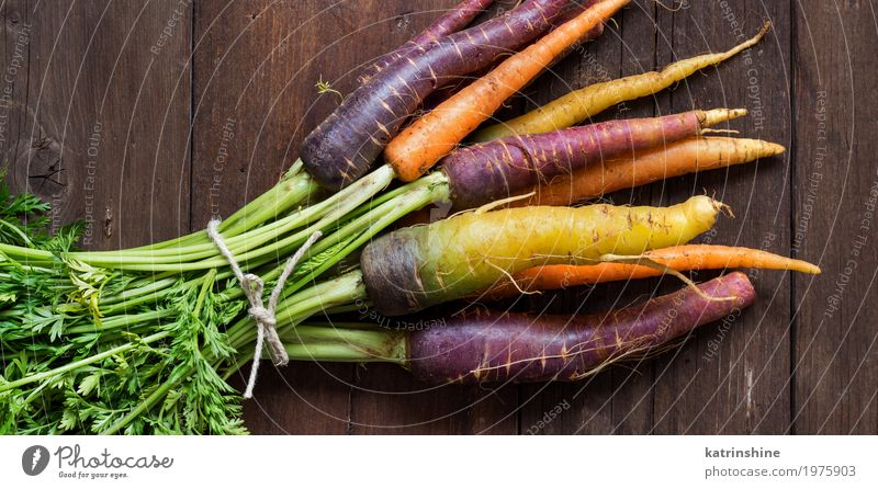 Fresh organic rainbow carrots on a wooden table Yellow Brown Nutrition Vegetable Harvest Vegetarian diet Diet Vitamin Farmer Root Carrot Raw Rustic Ingredients