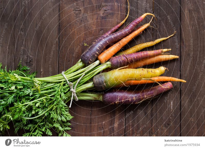 Fresh organic rainbow carrots with leaves on a wooden table Vegetable Nutrition Vegetarian diet Brown Yellow Carrot Farmer food Harvest healthy market orange