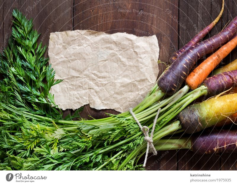 Fresh organic rainbow carrots and craft paper on wood Yellow Brown Nutrition Paper Write Vegetable Harvest Vegetarian diet Vitamin Farmer Root Carrot Raw Rustic