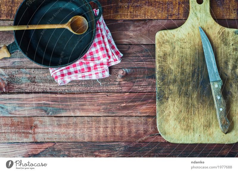 black cast iron pan and cutting board on brown wooden surface Old Black Dish Wood Brown Above Metal Vantage point Table Clean Kitchen Cloth Restaurant Crockery Steel Knives