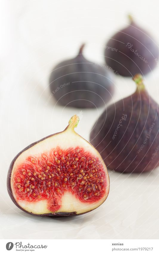 Four figs on a light background Fig Sliced Food fruit Vitamin Nutrition Vegetarian diet Fresh Healthy Violet Red White pseudo-fruit Studio shot Copy Space top