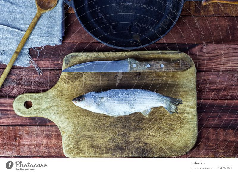 Frozen fish smelt on the kitchen board White Black Eating Natural Wood Food Brown Above Metal Fresh Table Fish Kitchen Knives Top