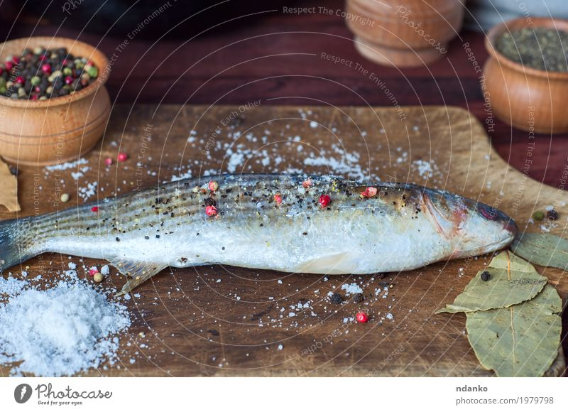 Fresh smelt fish in spices for cooking on a kitchen board Fish Herbs and spices Nutrition Eating Diet Table Kitchen Wood Above Brown White pepper paprika whole
