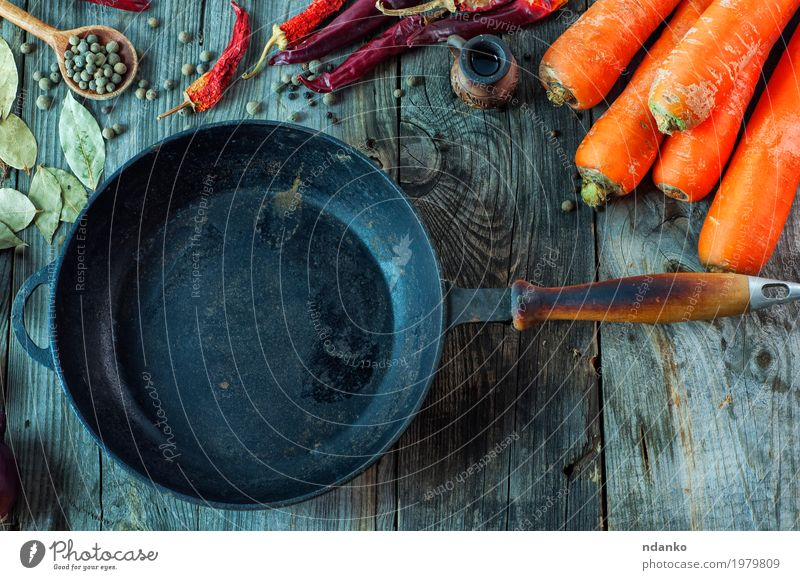 Black empty cast-iron frying pan among vegetables Dish Eating Wood Food Gray Orange Metal Nutrition Fresh Table Herbs and spices Kitchen Vegetable