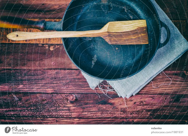 Empty frying pan on a brown wooden surface Crockery Pan Table Kitchen Tool Cloth Wood Metal Above Clean Brown Black tableware Tablecloth spatula copy