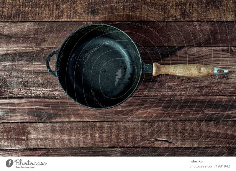 Black cast-iron frying pan on a brown wooden surface Crockery Pan Design Table Kitchen Restaurant Tool Wood Metal Above Clean Brown copy Vantage point Frying
