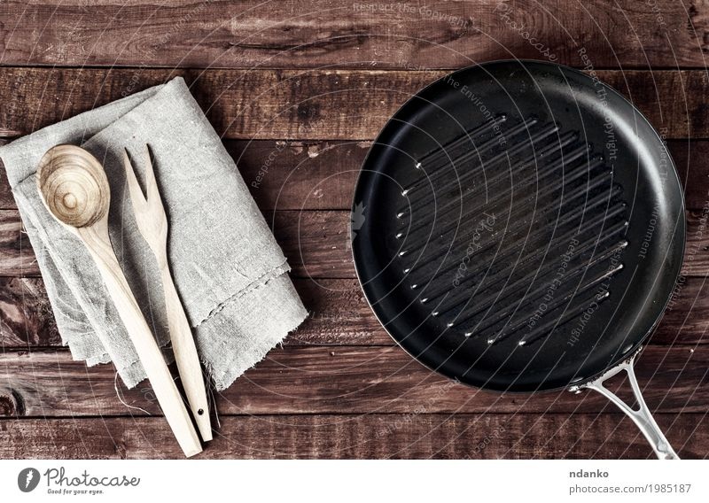 Empty grill pan with wooden spatula and spoon Old Black Dish Wood Brown Above Design Metal Vantage point Table Clean Kitchen Cloth Restaurant Crockery Top