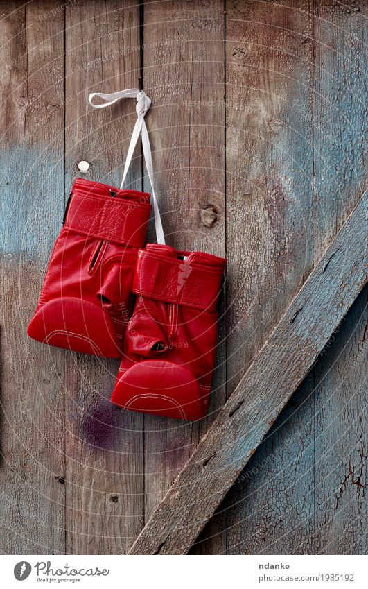 pair of red leather boxing gloves hanging on a nail Old Blue Red Sports Wood Retro Success Rope Symbols and metaphors Hang Shabby Conceptual design Competition