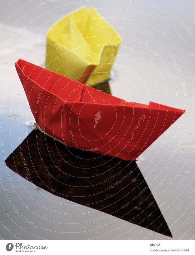 Ship ahoy! Yellow Red Paper boat Toys Reflection Lake Handicraft Playing Glide Germany Flag German Flag 2010 Colour photo Exterior shot Deserted