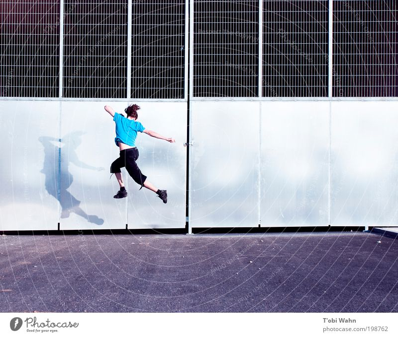 Now I'm jumping Joy Leisure and hobbies Human being Young man Youth (Young adults) 1 Gate Street Jump Free Thin Athletic Blue Tunnel entrance Grating Tall
