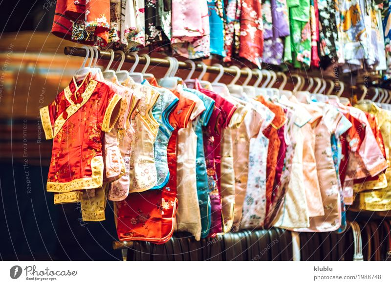 Different colored dresses hanging on a stand in a market. Shopping Beautiful Life Tourism Trip Landscape Dress Stand Small Modern colorful assortment retail