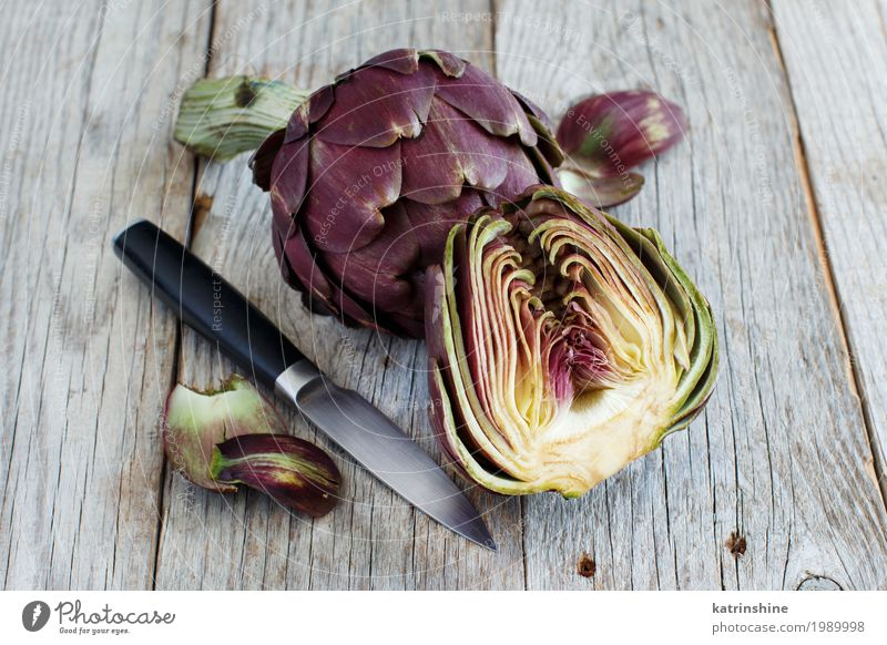 Roman Artichokes on a wooden board with knife Vegetable Nutrition Vegetarian diet Knives Fresh Gray Green agriculture Purple cooking Cut Edible food Half