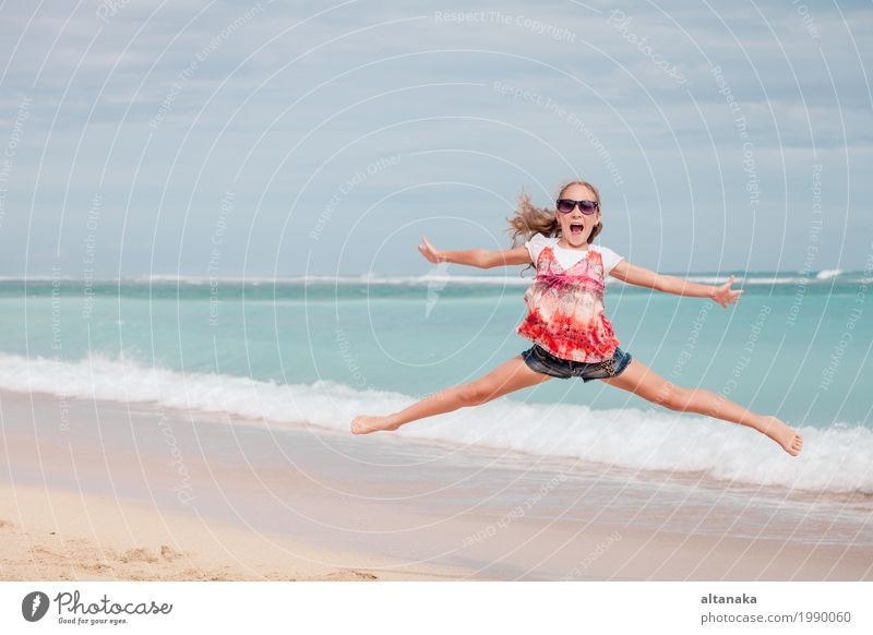 Happy teen girl jumping on the beach Lifestyle Joy Leisure and hobbies Playing Vacation & Travel Trip Freedom Summer Sun Beach Ocean Sports Child Girl Woman