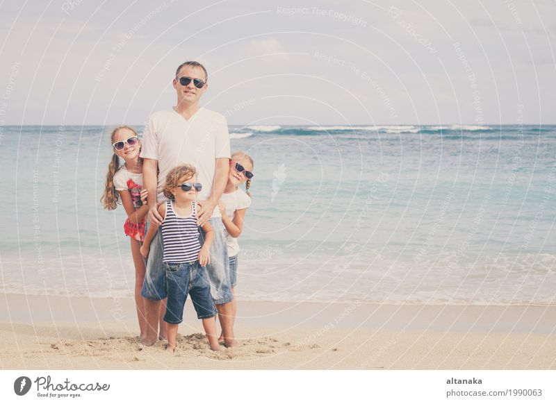Father and children playing on the beach at the day time. Concept of friendly family. Lifestyle Joy Relaxation Leisure and hobbies Playing Vacation & Travel