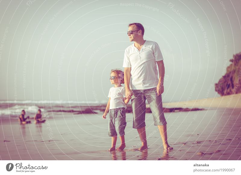 Father and son playing on the beach at the day time. Concept of friendly family. Lifestyle Joy Relaxation Leisure and hobbies Playing Vacation & Travel Trip