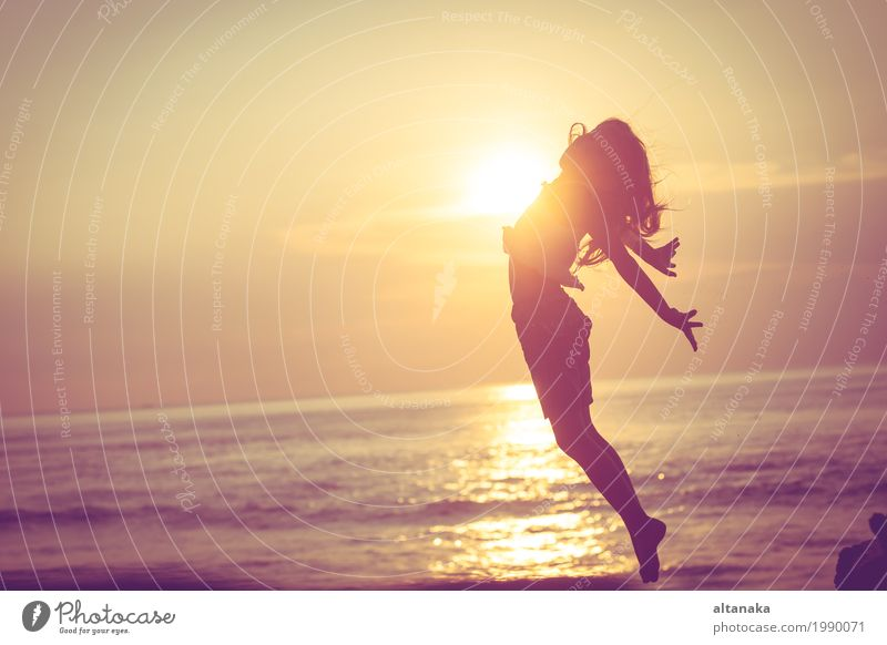 Happy little girl jumping on the beach at the sunset time Lifestyle Joy Leisure and hobbies Playing Vacation & Travel Trip Freedom Summer Sun Beach Ocean Sports