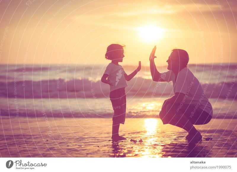 Father and son playing on the beach at the sunset time. Concept of friendly family. Lifestyle Joy Leisure and hobbies Playing Vacation & Travel Trip Freedom