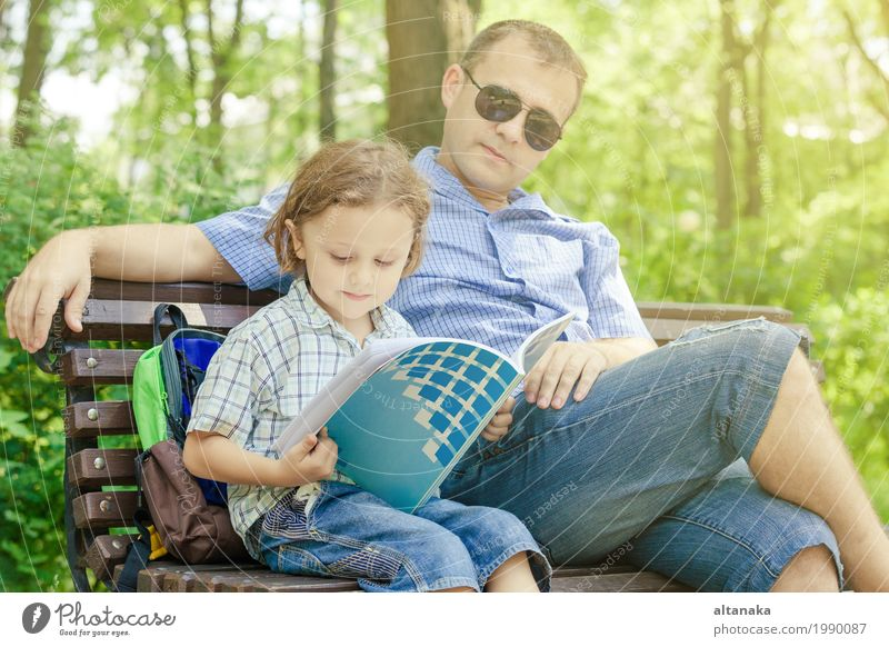Father and son playing at the park on bench at the day time. Lifestyle Joy Relaxation Leisure and hobbies Playing Reading Vacation & Travel Freedom Summer Sun