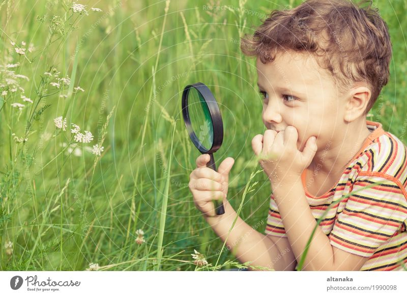 Happy little boy exploring nature with magnifying glass at the day time Lifestyle Joy Face Playing Summer Garden Science & Research Child School Human being