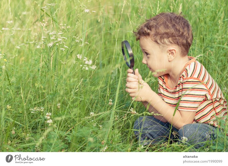Happy little boy exploring nature with magnifying glass Human being Child Nature Plant Summer Green Hand Flower Joy Face Lifestyle Meadow Grass Boy (child)