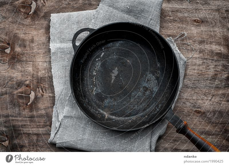 Empty black cast-iron frying pan Crockery Pan Table Kitchen Restaurant Cloth Wood Metal Above Clean Brown Black tableware Tablecloth Vantage point Frying