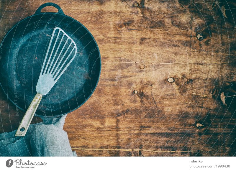 Black empty frying pan with an iron spatula Old Dish Wood Brown Above Metal Vantage point Table Clean Kitchen Cloth Restaurant Crockery Top Tool