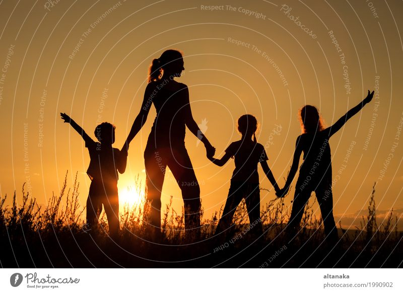 Happy family standing in the park at the sunset time. Lifestyle Joy Beautiful Leisure and hobbies Playing Vacation & Travel Trip Freedom Camping Summer Sun