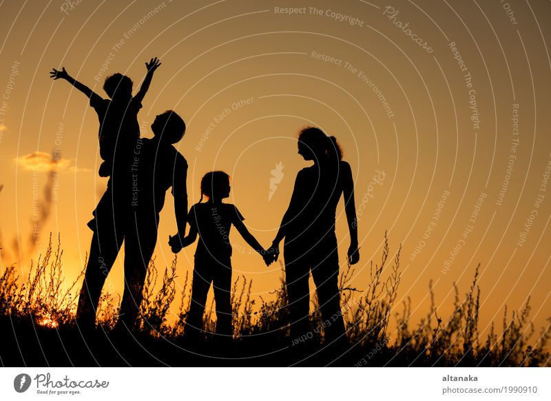 Happy family standing in the park at the sunset time. Child Woman Nature Vacation & Travel Man Summer Beautiful Sun Hand Joy Girl Adults Lifestyle Love Grass