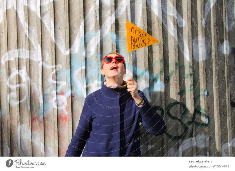 Woman in a coat with glasses and pennant in front of a graffiti wall made of concrete Lifestyle Feasts & Celebrations Birthday Feminine Young woman