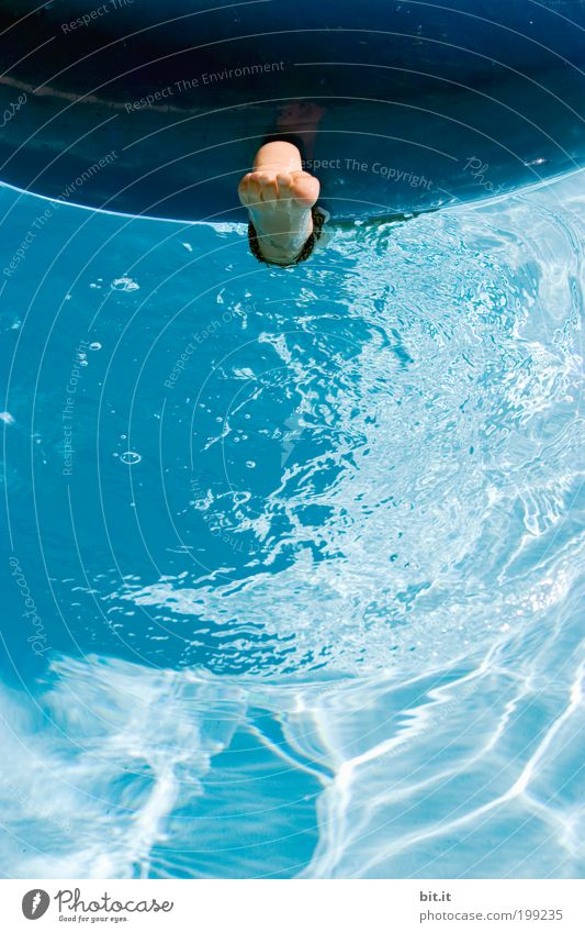 Naked foot hangs alone in the blue water under a swimming tire, in the swimming pool, in summer on vacation. Joy Well-being Contentment Swimming & Bathing