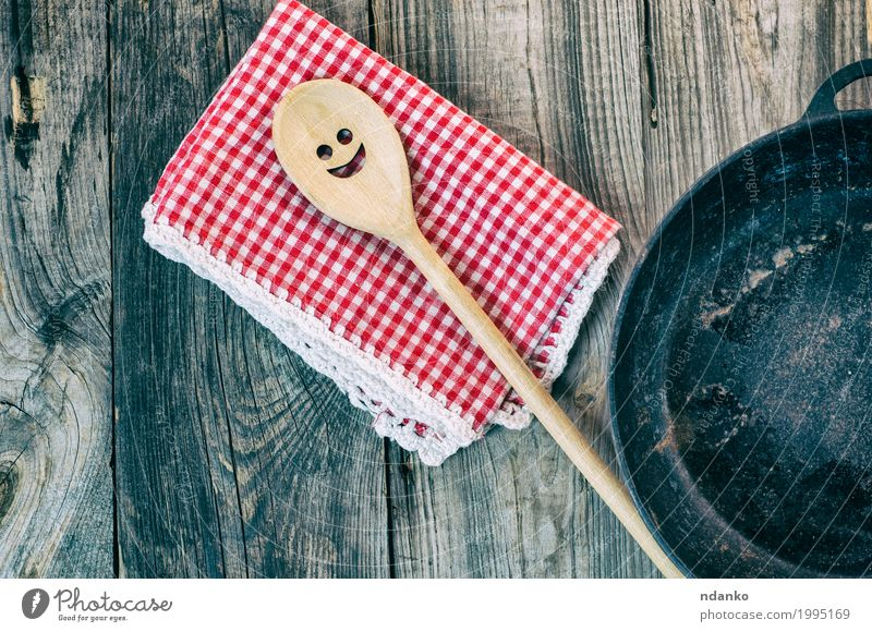 Black cast-iron frying pan with a wooden spatula Crockery Pan Spoon Table Kitchen Restaurant Tool Cloth Wooden spoon Metal Above Clean Brown Gray Red Happy