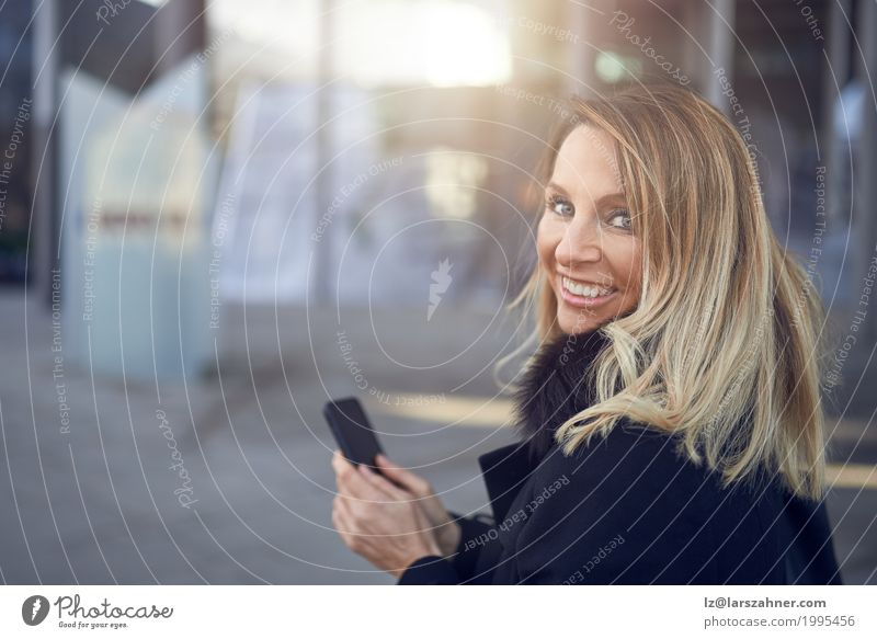 Smiling attractive woman looking over her shoulder Happy Face Business Telephone PDA Woman Adults 1 Human being 30 - 45 years Town Street Blonde Friendliness