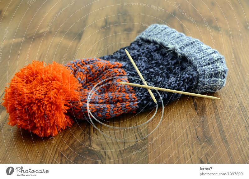 knitting woolly hat. finished hat on table. with needles Leisure and hobbies Warmth Fashion Cap Wool Knit Creativity creased yarn handmade The Needles