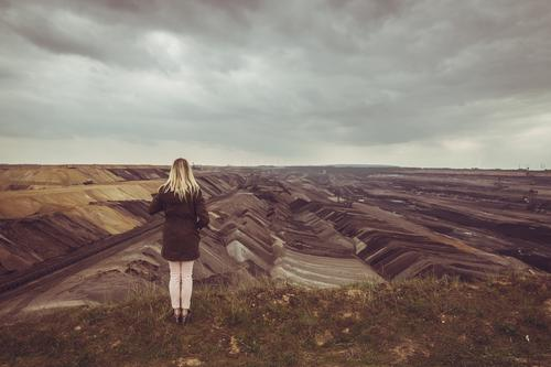Blonde woman looking at open pit coal mine Energy industry Energy crisis Young woman Youth (Young adults) Woman Adults 1 Human being Environment Earth Clouds