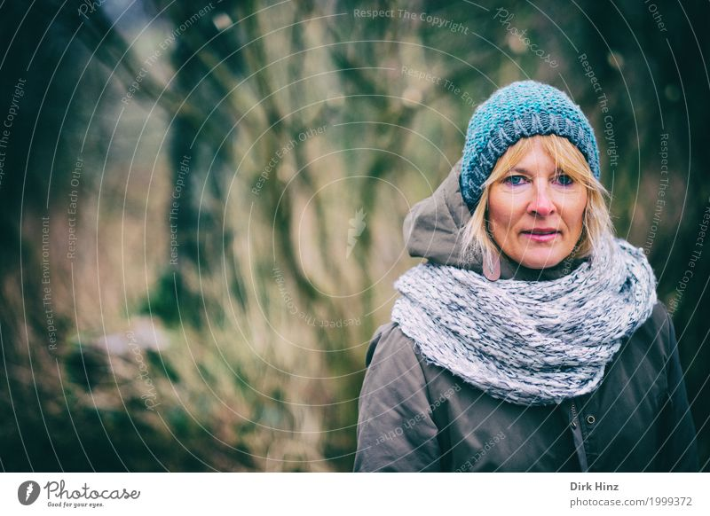 Woman with cap in cold season Human being Feminine Adults Life 1 45 - 60 years Jacket Blonde Uniqueness natural Blue Looking Observe Forest To go for a walk