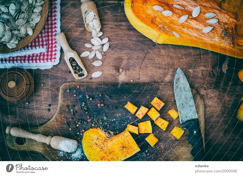 Pieces of pumpkin in salt and pepper Eating Wood Health care Food Brown Above Orange Nutrition Fresh Herbs and spices Vegetable Top Vegetarian diet Spoon