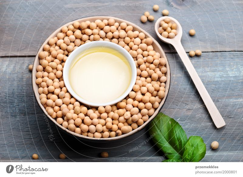 Soy beans and soy oil in bowls on wooden table Grain Nutrition Organic produce Vegetarian diet Asian Food Bowl Spoon Container Wood Fresh Healthy Natural Beans